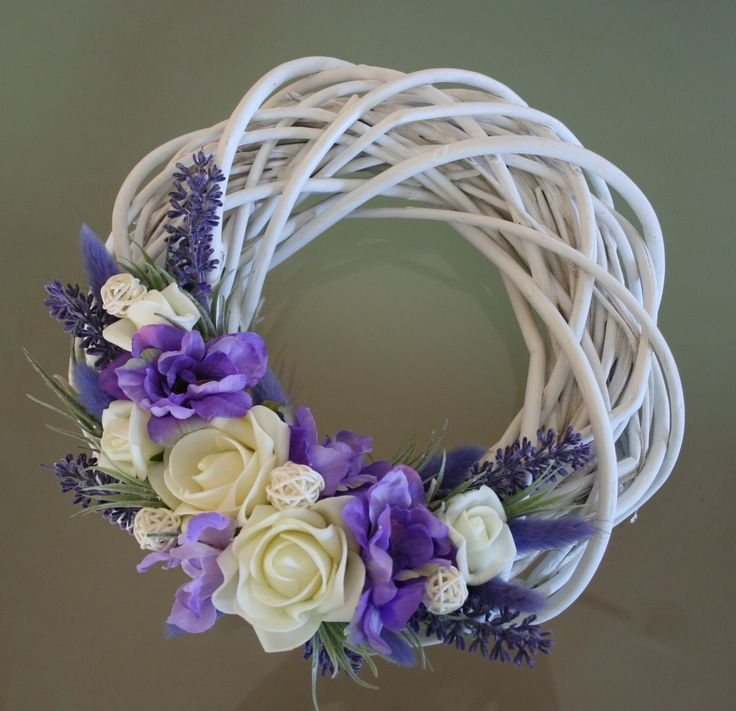 Bílý proutěný věneček do fialkova Bílý proutěný věneček v bílých a fialkových odstínech na bílém proutěném korpusu o průměru 25 cm, zdobený látkovými květy a pěnovými růžičkami, umělou levandulí, ratanovými kouličkami a sušinou.