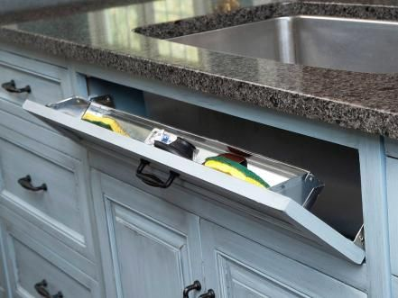 "To really maximize the storage in your kitchen, put unused areas to work. Typically, the ""drawer"" in front of the kitchen sink is just a false front, but with the addition of cleverly hidden hinges and a stainless steel tray, it becomes out-of-sight storage for wet sponges and scrub brushes. Photo courtesy of Mullet Cabinets, Inc."