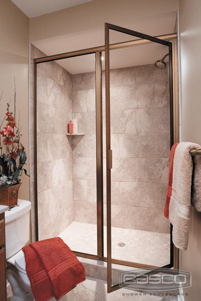 deluxe framed pivot door and inline panel featuring brushed bronze finish and clear glass glass shower