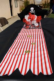 Table runner decorations for pirate birthday party. Black plastic tablecloth with red and white striped runner - genius!