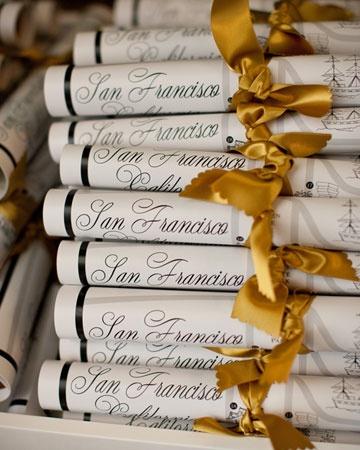 Scrolls of programs, wrapped with gold ribbon  #themodernjewishwedding.com via @Martha Stewart Weddings Magazine