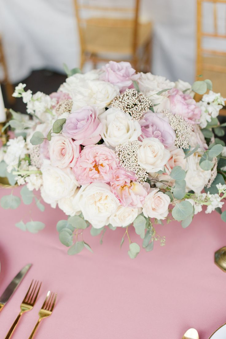 Organic garden-style wedding centerpiece designed by Courtney Inghram Events in Virginia, with blush garden roses, rice flower, white stock, pink roses, eucalyptus, ranunculus, scabiosa, with gold accents for outdoor vineyard wedding. With photo by Lauren Simmons Photography