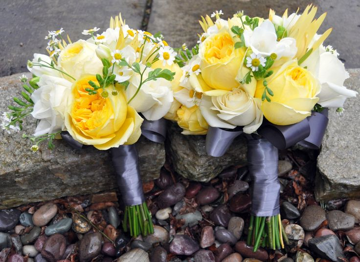 Bridesmaid and Bride wedding bouquets in yellow, white and grey.