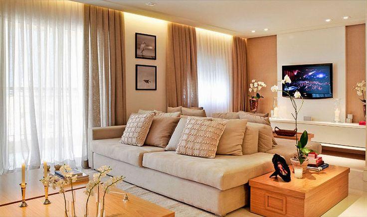O painel da TV em branco laqueado, combinando com o rack e ganha destaque centralizado na parede revestida com papel de parede cor de juta c...