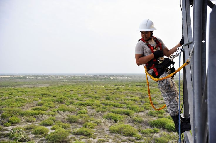 Senior Airman Daniel Reyes, 47th Communications Squadron airfield systems technician, hangs off the side of a Digital Assault Stratification Radar tower on Laughlin Air Force Base, Texas, July 24, 2014. Laughlin's Airfield Systems Airmen maintain approximately $6.5 million in equipment including 180 different types of radios, two instrument landing systems, one navigation system and two full weather systems that support flight line and base wide operations. (USAF Senior Airman Nathan…