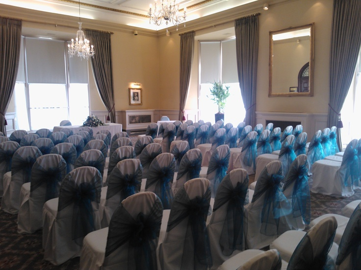 Peacock organza sashes on white chair covers at the Crown Hotel