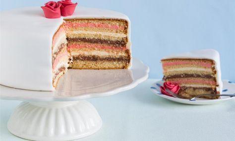 Zo maak je met een pudding, botercrème en chocoslagroom een vrolijk gekleurde vanillecake laagjestaart. Decoreer met fondantroosjes.