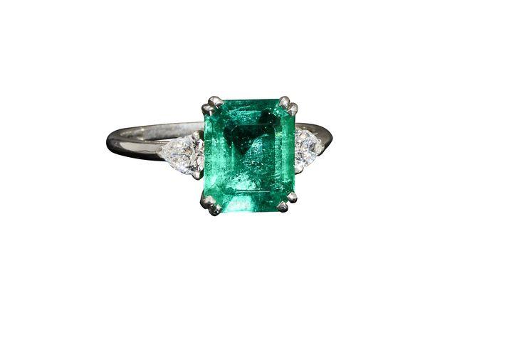 Klassieke ring bezet met emeraude geslepen smaragd van 2,65 ct geflankeerd door twee druppel-vormig geslepen diamanten van elk 0,45 ct. Te zien bij Hemke Kuilboer Juweliers.