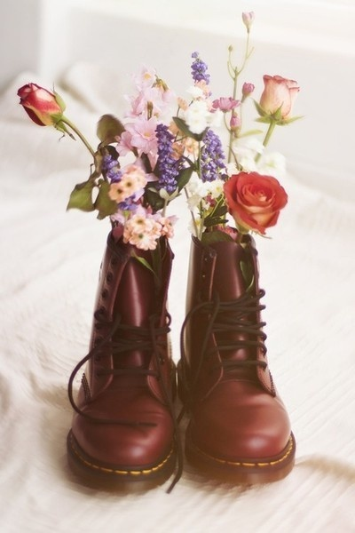 a pair of doc martens as a vase for flowers