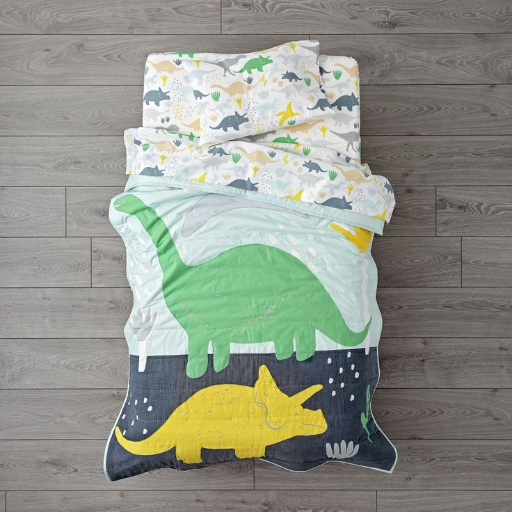 Shop Dinosaur Toddler Bedding.  Our Dinosaur Toddler Bedding includes a blue baby quilt with multicolor print and embroidered dinos.