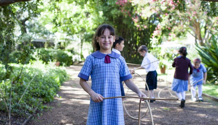 School girl playing with an old-fashioned stick and hoop game