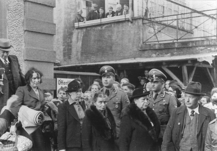 German SS watch roundup of Jews in Lorrach, Germany October 22, 1940 In this photo, citizens of a small town watch police lead Jewish men and women to trucks for deportation from Germany. Children peek from behind the line of deportees while adults witness the event from a balcony above. These Jews of Lörrach were transported to German-occupied France. In 1942, German officials, with French collaboration, later deported most of them to Auschwitz. Few survived. World War Two
