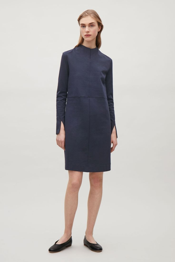 Designed with a standing, overlapping neckline and with twisted sleeve seams, this dress is made from a comfortable cotton-mix. A close fit, it is completed with long sleeves, a straight hemline and a hidden back zip.