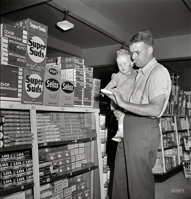 """May 1942. """"Greenbelt, Maryland. Father and son shopping in the cooperative store. Photo by Marjory Collins for the Resettlement Administration"""