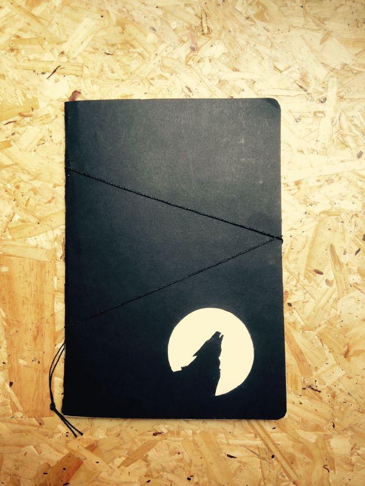 Caderno artesanal preto com fechamento em barbante. Na capa um recorte da silhueta de um lobo uivando e papel triplex para a lua.