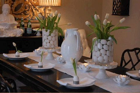For a clean, sophisticated look, place glass hurricanes atop ruffled cake stands, and fill with plain white eggs and crisp white tulips. See more at Decor Pad.