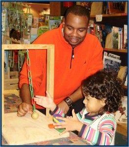Preschool special education teacher Jaumall Davis observes a child in his inclusive classroom working with a pendulum