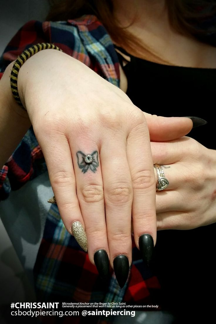 Microdermal Piercing on the Finger... in a Bow Tattoo. Chris Saint.