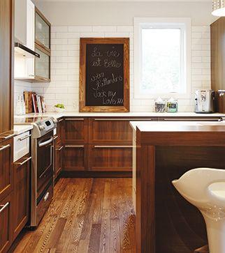 Cuisine avec l'imposant tableau noir et le plancher en frêne à la couleur riche.
