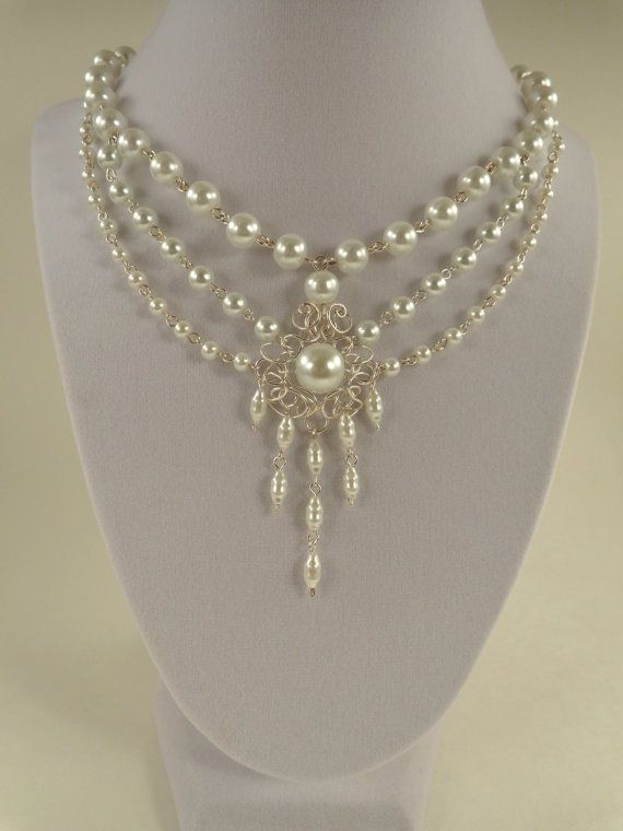 This beautiful and elegant necklace displays an array of shapes and sizes of white pearls with a central, chandelier style setting, for