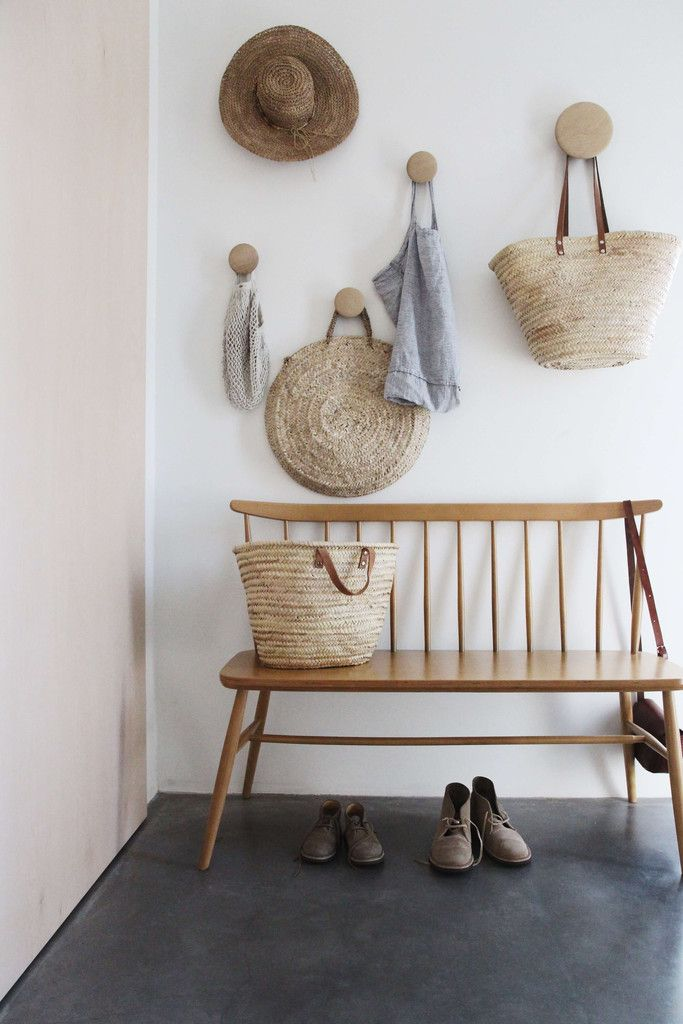 Casual entryway with wood bench and hooks.