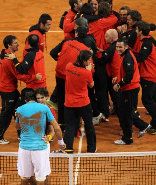One of the most enduring Sports Images of 2011. After Spain had beaten Argentina in the Davis Cup finals in front of Roaring Home Crowd,the Spanish Contingent barged on the Clay Court to celebrate with Rafa.  But before celebrating he consoled and had a chat with Del Potro who looked devastated after the loss. What a Sporting Moment ! Rafa, what a Champion !