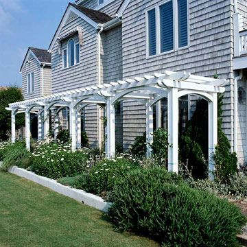 Backyard Landscaping Ideas Garden Structure Attached Pergola: A pergola is a natural way to connect a home to the landscape. Here, a long, narrow pergola is painted crisp white to match the trim of the house. Low-growing shrubs form attractive mounds of foliage and flowers at the base of the pergola.