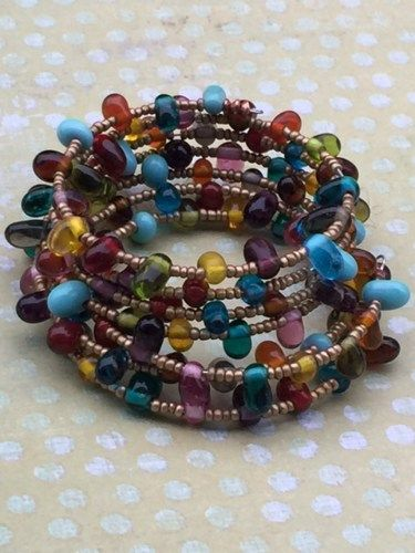 Bohemian Rhapsody Beaded Wrap Bracelet featuring a huge array of multicolored glass and gold-tone beads. There are six beautiful rows of colorful beads that will dance around your arm. Take notice of
