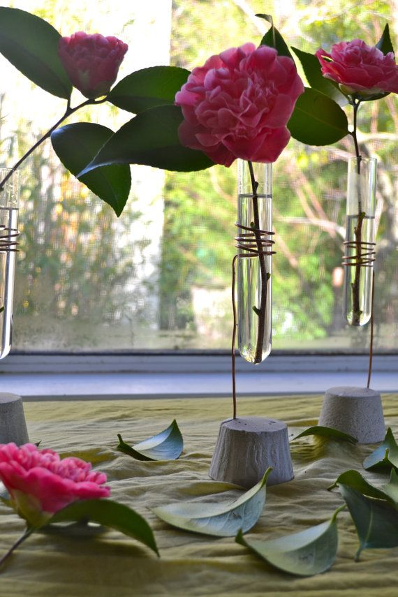 Add fresh flowers or herbs to your dinner table, or bedside with this elegant yet simple bud vase. The base is made from concrete and the vase is a re-purposed glass test tube with salvaged copper wire wrapped around it. These also make great table settings for large or small events! The size of the base is approximately 2.5 and the height is 10.  Made In Sonoma County, California