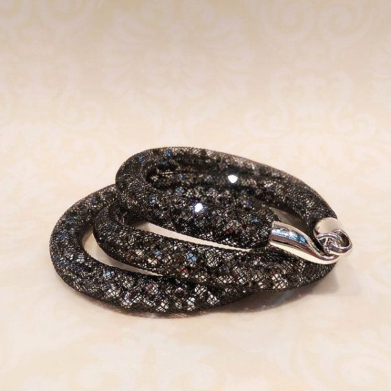 This glamorous bracelet is uniquely designed with hundreds of sparkle bicone crystals (in metallic silver) filled in a black mesh tube and
