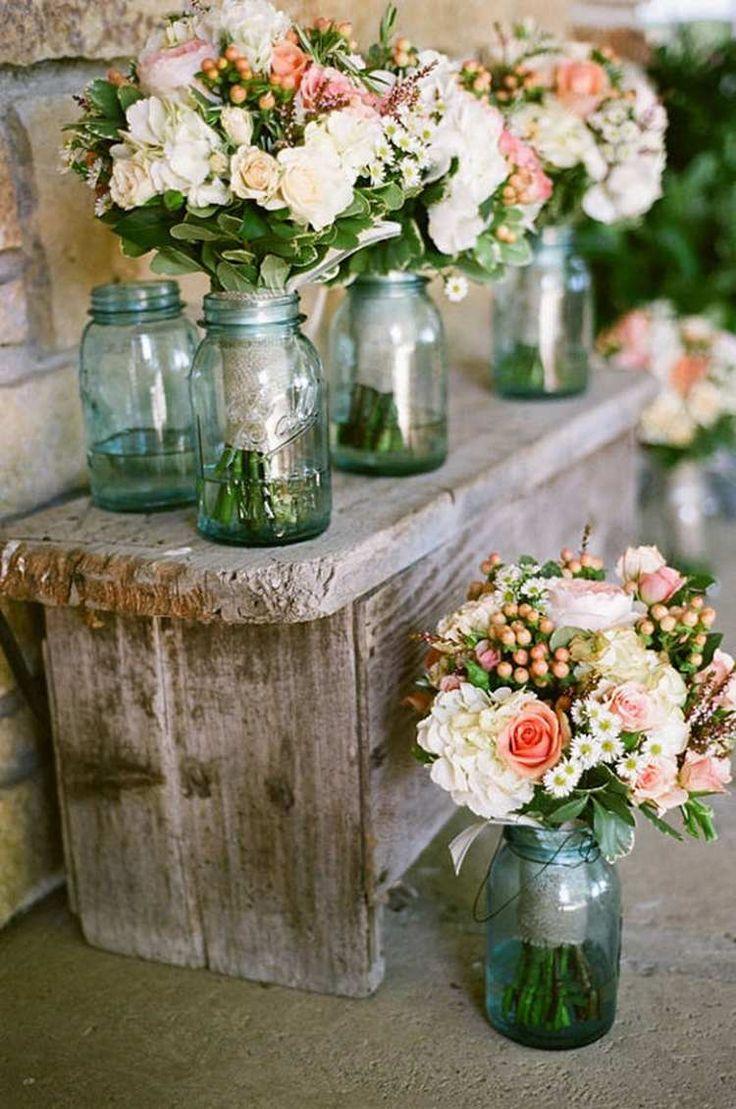 déco mariage champêtre - banc en bois rustique, bocaux de verre bleu et bouquets de fleurs en blanc et rose