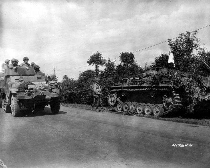 https://flic.kr/p/8q9SAp | p013130.jpg | Un Half-Track  M3A1 passe,  le 13 août 1944, sur une route du bocage à Saint Germain de Tallevende (5 km au sud de Vire), devant un Stug III (canon automoteur allemand) Le Stug III est garé le long de la route, il  est muni d'un drapeau blanc, deux GI's  sont descendus pour voir de plus près le blindé. Sous réserve un blindé de la Sturmgeschütz-Brigade 394, cantonnée à Azay-le-Rideau le 6 juin, attend de percevoir ses matériels, 31 StuG III, avant de…