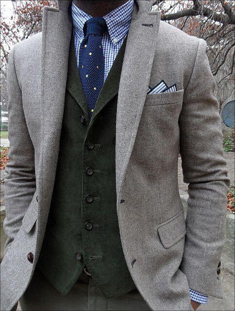ライトグレーのツイードスーツにくすんだダークグレーのベスト、ネイビーのネクタイ、ギンガムチェックのシャツを合わせた着こなし
