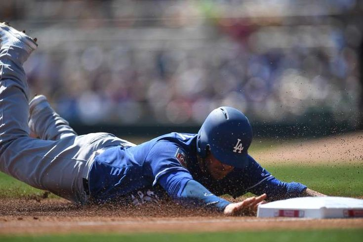 2018 MLB spring training - SLIDING THROUGH:   Dodgers catcher Yasmani Grandal (9) slides into third base against the White Sox on March 2 in Phoenix, AZ. Los Angeles won 7-6.