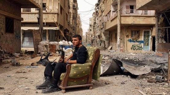 """""""Y en el sillón, el guerrero. No lleva uniforme del ejército sirio, sino que va vestido de negro polvoriento, como van unas, u otras, de las distintas milicias rebeldes""""."""