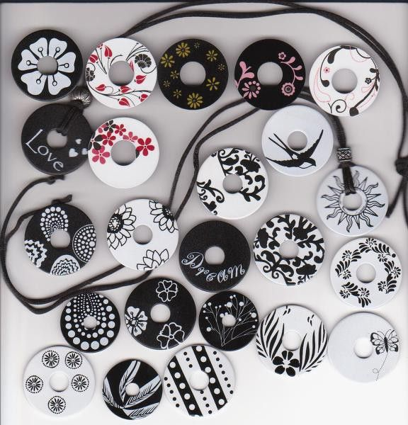 Made with rub-ons. They are just plain old washers from the hardware store.  Spray paint them, add the rub-ons, then spray a clear coat on them.