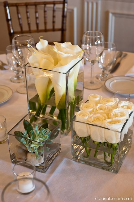 Simple and beautiful: White roses cut short and lined up in short square glass container, taller square with taller white callas and some kind of succulent in smallest square vase