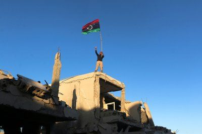 2016 in review: 50 powerful photos of war in Syria, Iraq, Libya and Yemen:      6 December 2016: A fighter of Libyan forces allied with the UN-backed government waving a national flag flashes a victory sign as he stands atop the ruins of a house after forces finished clearing Ghiza Bahriya, the final district of the former Islamic State stronghold of Sirte. Hani Amara/Reuters