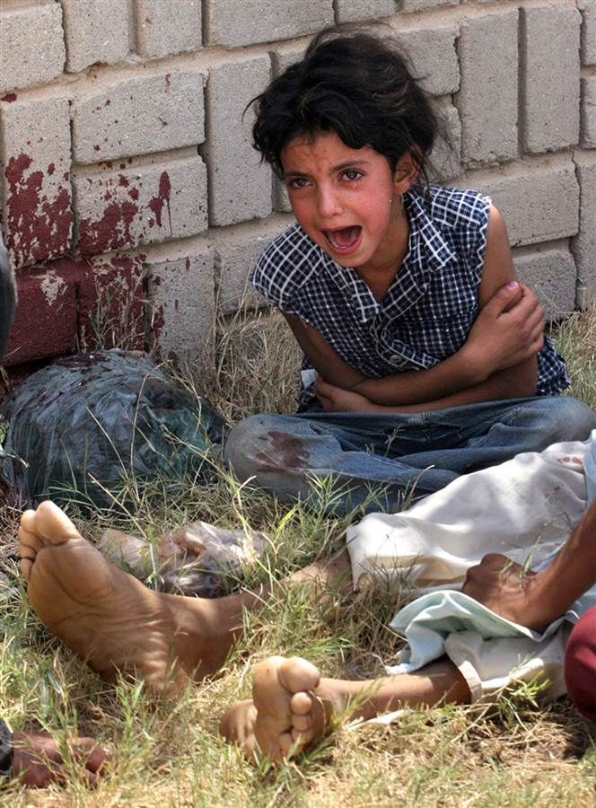 One of the two daughters of Jalil Shaalan, a security guard at a school, reacts after her father was gunned down in front of them outside of the school compound by unknown gunmen in the Amarayah district of Baghdad on July 21, 2005. Hadi Mizban / AP