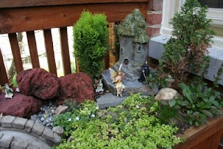 Delightful 'fairy garden' built buy a grandpa for his granddaughters on his own deck.  Adorable and child friendly to be able to 'play act' in.