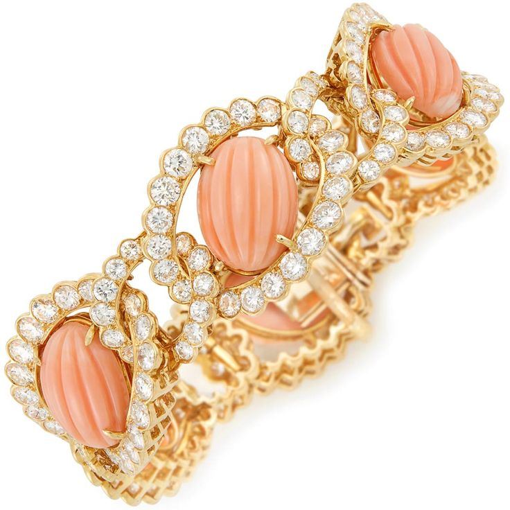 Gold, Carved Coral and Diamond Bracelet, Van Cleef & Arpels 18 kt., centering 6 oval carved corals approximately 15.8 x 11.5 mm., framed by interlocking loops of 192 round diamonds approximately 20.00 cts., signed Van Cleef & Arpels, N.Y., no. 38525, partially obscured, with French import mark, approximately 43 dwts. Inner circle 6 1/4 inches. With signed box.  Estimate: $60,000 - $80,000