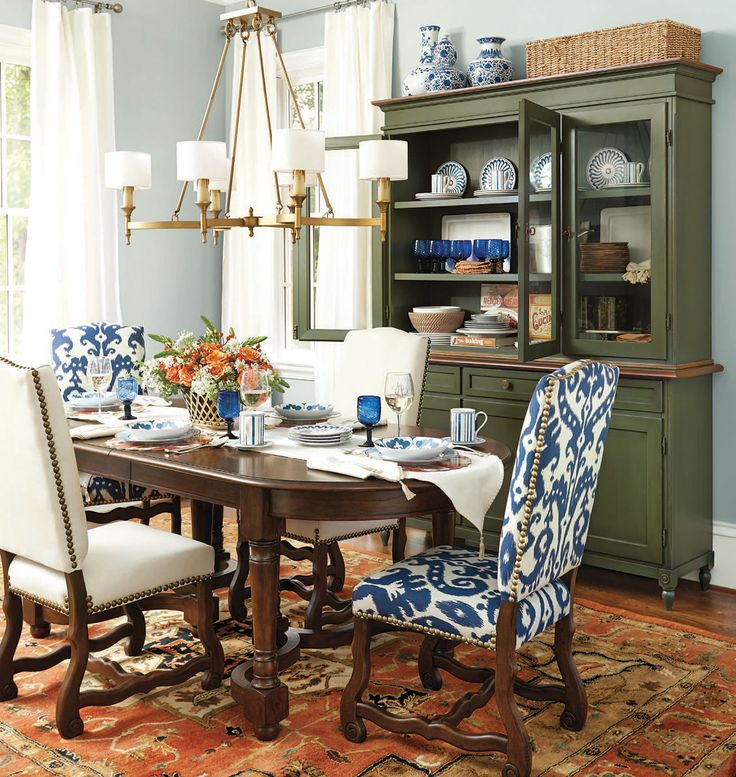 Deep, saturated colors bring drama to this dining room, like a red rug, navy dining chairs, and a green hutch.