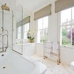 Stunning master bathroom with mushroom linen roman shades, floor-mount towel warmer, ...