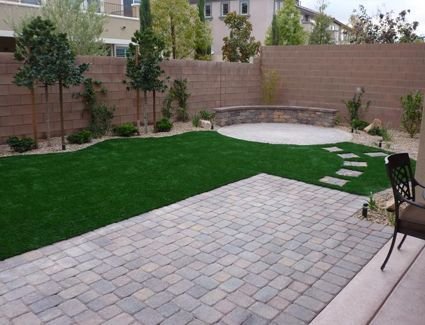 Paver extension off of concrete patio. Fire pit/seating area. Trees line fence.
