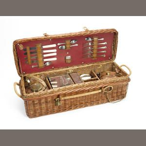 A G W Scott & Sons four person compact wicker picnic set, circa 1908, wicker picnic basket with red interior and makers stamping logo to inside of the lid, fully fitted with copper kettle and burner, sandwich box and food boxes, 1907 hallmarked silver Vesta case, ceramic butter jar with lid held in place with leather strap, glass milk bottle, cutlery housed in leather straps in the lid.  Sold for £2,300 inc. premium