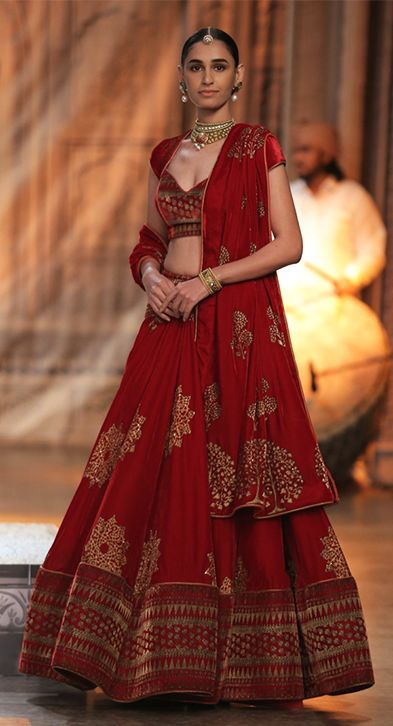 A model displays a gorgeous red lehenga at an FDCI ICW 2016 event. (Source: aienjamir.com)