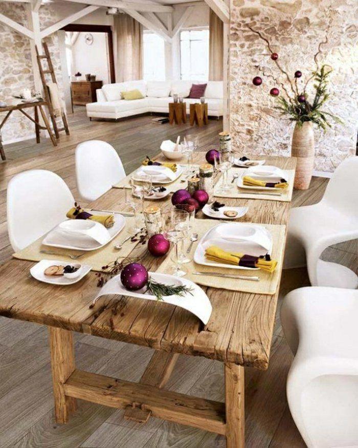 mur en fausse pierre et table en bois clair , chaises plastiques blanches