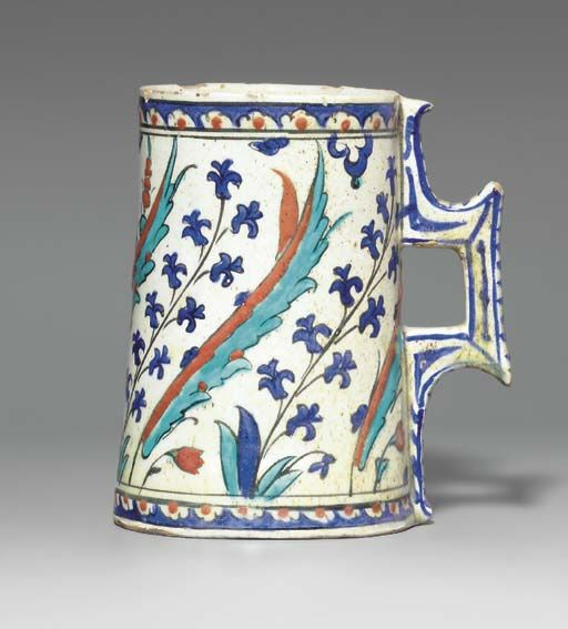 AN IZNIK POTTERY TANKARD  OTTOMAN TURKEY, CIRCA 1590  Of tapering cylindrical form with angular handle, the white body decorated in cobalt-blue, bole-red, turquoise and black outline with alternating large saz leaves and blue hyacinths curving to the left, the base and mouth with a narrow band of white and red half-rosettes on blue ground,   7¼in. (18.6cm.) diam.