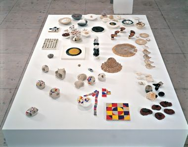 Working Tables, 2000‑2005; unfired clay, straw, egg container, bottle caps, wiremesh screen, string, stones, shells, plaster, bark, polystyrene foam, painted wood elements, pizza dough, and other materials, dimensions variable. Courtesy of the artist and MoMA, New York.