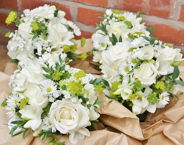 Dainty, rustic bridesmaids' bouquets of white avalanche roses, white freesia, white gypsophila, green bupleurum and white daisy aster. Florissimo - Flowers for weddings, events and businesses in Shropshire and beyond.